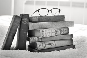 Pile of books with glasses on top