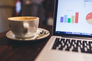 Google Analytics On Laptop With Coffee Cup Nearby